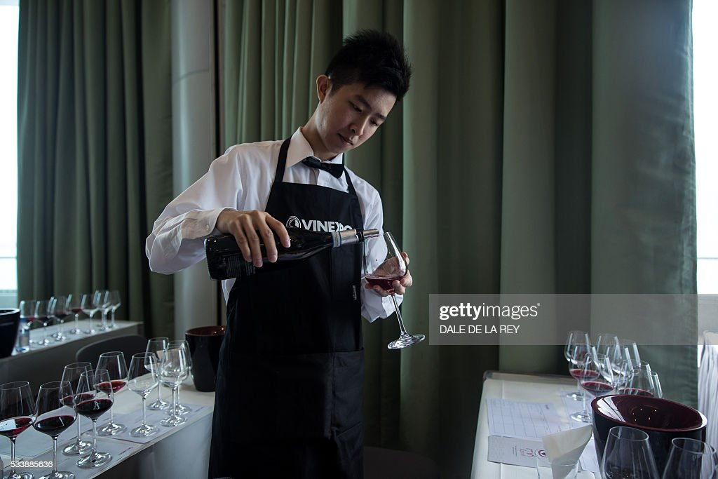 A waiter pours a glass of wine during a tasting event at Vinexpo in Hong Kong on May 24, 2016. The international wine and spirits exhibition runs from May 24 to 26. / AFP / DALE