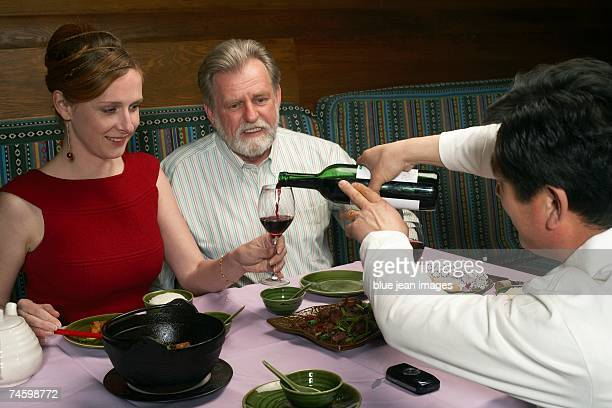 Waiter pours wine for woman at a Chinese restaurant.