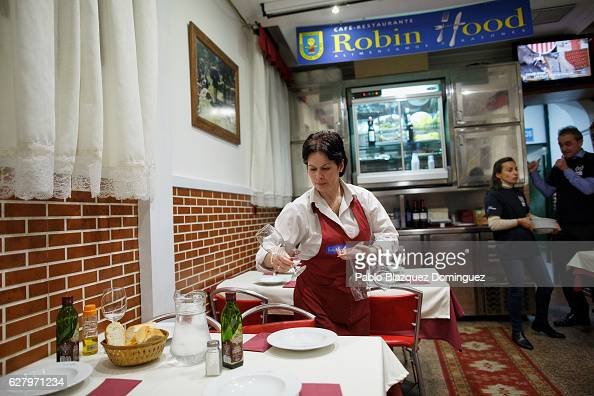 A waiter prepare tables before homeless people enter to have a free dinner at Robin Hood restaurant on December 5 2016 in Madrid Spain Association...