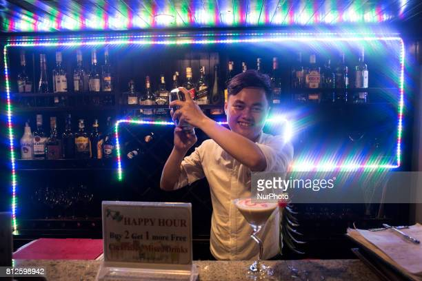 A waiter prepares a cocktail in one of the hundreds of tourist cruises that cross the bay of Ha Long The bay of Ha Long is an extension of water of...