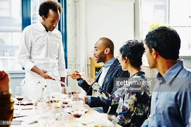 Waiter presenting bill on digital tablet to table