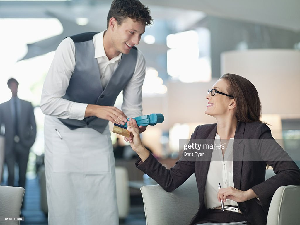 Waiter processing businesswomans credit card with credit card reader : Stock Photo