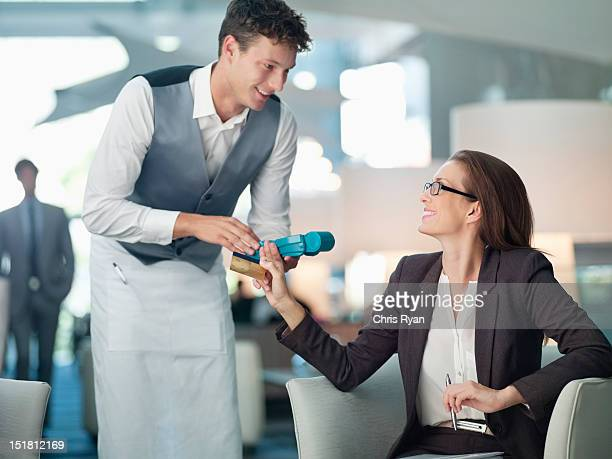 Waiter processing businesswomans credit card with credit card reader