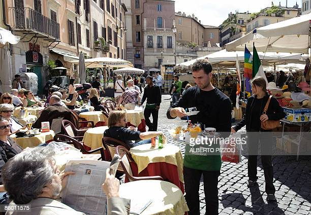 A waiter serves a freshly brewed espresso at a cafe terrace on Campo dei Fiori in centre Rome on April 17 2009 during the 'Espresso Italiano day...