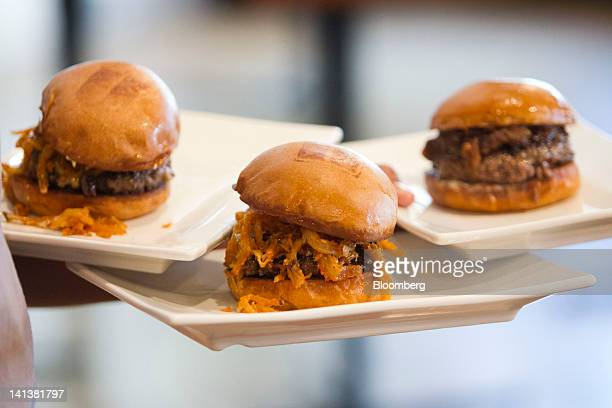 A waiter serves a trio of burgers including in the center the Manly Burger made with beercheddar cheese smokedsalt onion strings and bacon lardons...