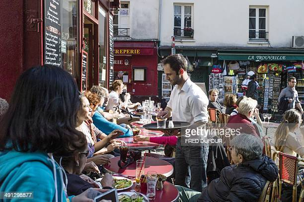 A waiter serves clients in a cafe of the Montmartre neighborhood in the city of Paris on May 16 2014 AFP PHOTO / FRED DUFOUR