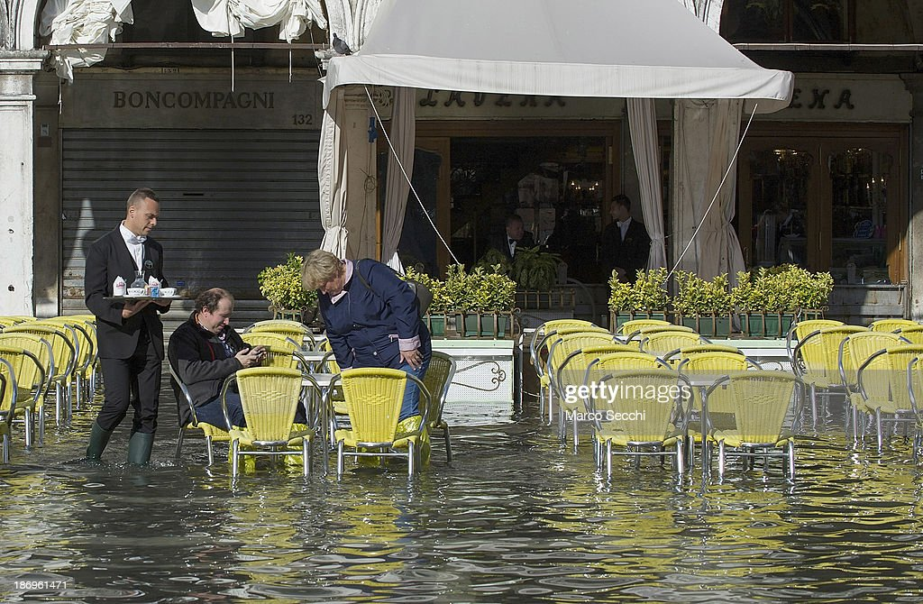 A waiter serves coffee to a couple at a Cefe in Saint Mark's Square during today's Acqua Alta on November 5, 2013 in Venice, Italy. The high tide, or acqua alta as it is locally known, is a natural event most commonly affecting the city during Autumn and Winter.
