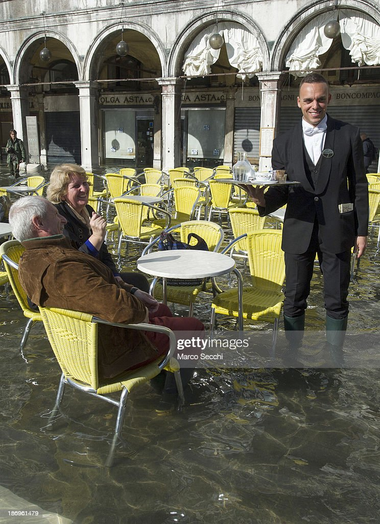 A waiter serves coffee to a couple in Saint Mark's Square during today's Acqua Alta on November 5, 2013 in Venice, Italy. The high tide, or acqua alta as it is locally known, is a natural event most commonly affecting the city during Autumn and Winter.