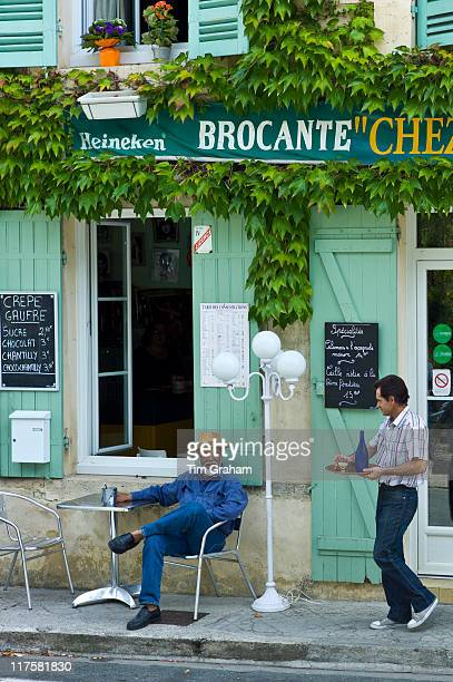 Waiter serves customer Pastis at traditional French Cafe in town of Castelmoron d'Albret in Bordeaux region Gironde France