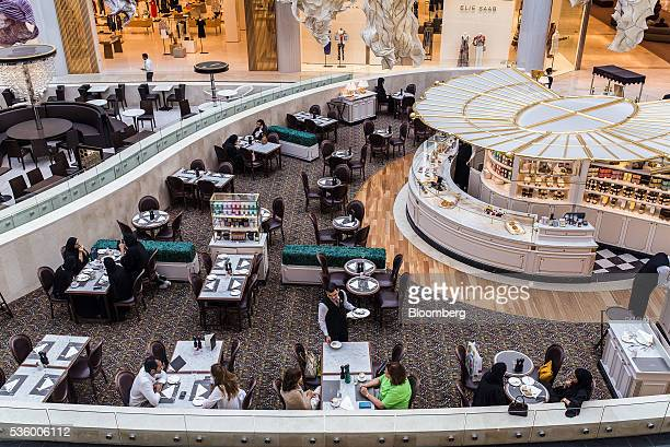 A waiter serves customers in a coffee shop at the Yas Island Mall in Abu Dhabi United Arab Emirates on Monday May 30 2016 Abu Dhabi which sits on six...