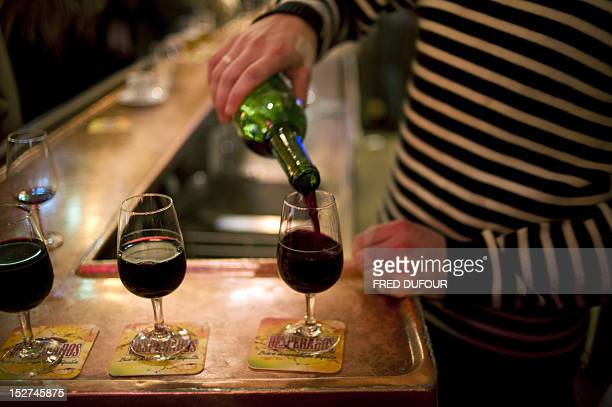 A waiter serves glasses of red wine at the counter of a bar on December 2 2011 in Paris AFP PHOTO / FRED DUFOUR