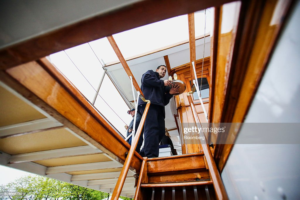 A waiter serves guests aboard the Land Rover hospitality boat ahead of the Louis Vuitton America's Cup World Series races in New York, U.S., on Friday, May 6, 2016. The America's Cup sailing races are held in New York City on the Hudson River for the first time since 1920. Photographer: Chris Goodney/Bloomberg via Getty Images