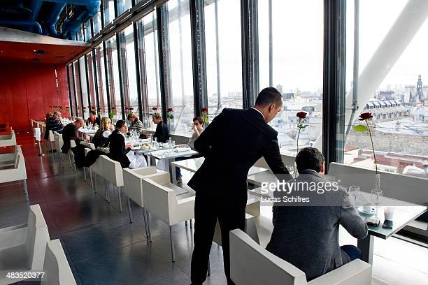 A waiter serves patrons who enjoy the view in restaurant Georges in Paris France on November 7 2013 Restaurant Le Georges is one of the two trendy...