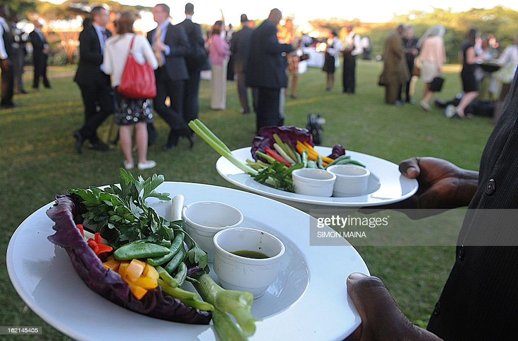 A waiter serves rejected green salad, grown by Kenyan farmers but rejected by UK supermarkets due to cosmetic imperfections, on February 19, 2013 during the Governing Council of the United Nations Environment Programme (UNEP) at the UN headquarters in Nairobi. The campaign aims to promote actions by consumers and food retailers to dramatically cut the 1.3 billion tonnes of food lost or wasted each year -- which, aside from the cost implications and environmental impacts, increases pressure on the already straining global food system -- and help shape a sustainable future. AFP PHOTO / SIMON MAINA