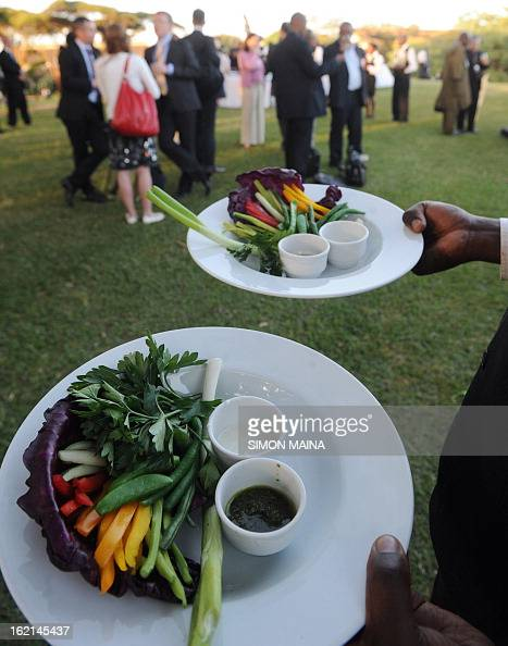 A waiter serves rejected green salad grown by Kenyan farmers but rejected by UK supermarkets due to cosmetic imperfections on February 19 2013 during...
