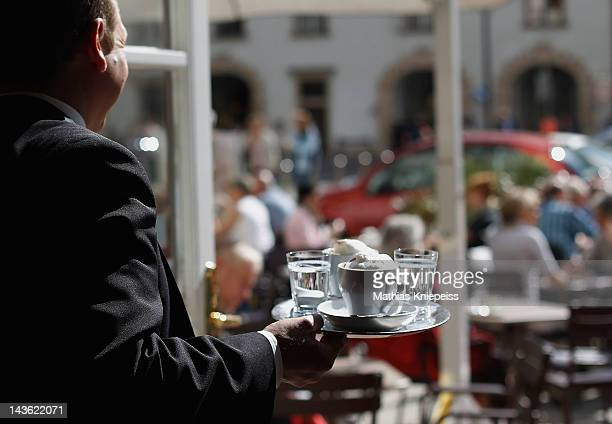 A waiter serves two Kleine Braune coffees at Cafe Hofburg on April 25 2012 in Vienna Austria Cafe Hofburg which opened its doors in 2004 is one of...