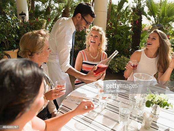 A waiter serves wine to four beautify ladies sit around a garden table in San Diego.