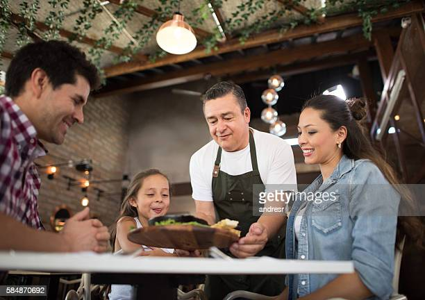 Waiter serving a family at restaurant