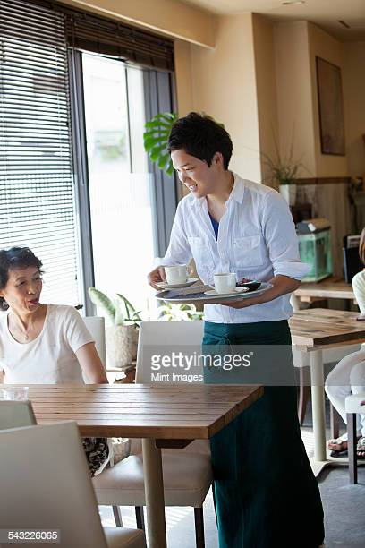 Waiter serving a woman seated at a table in a cafe.