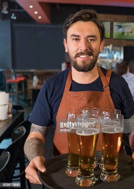 Waiter serving beer at  a bar