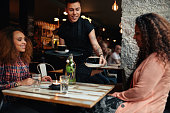 Waiter serving coffee to young women at restaurant. Two female friends at coffee shop.