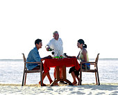Waiter serving couple at beach dinner table