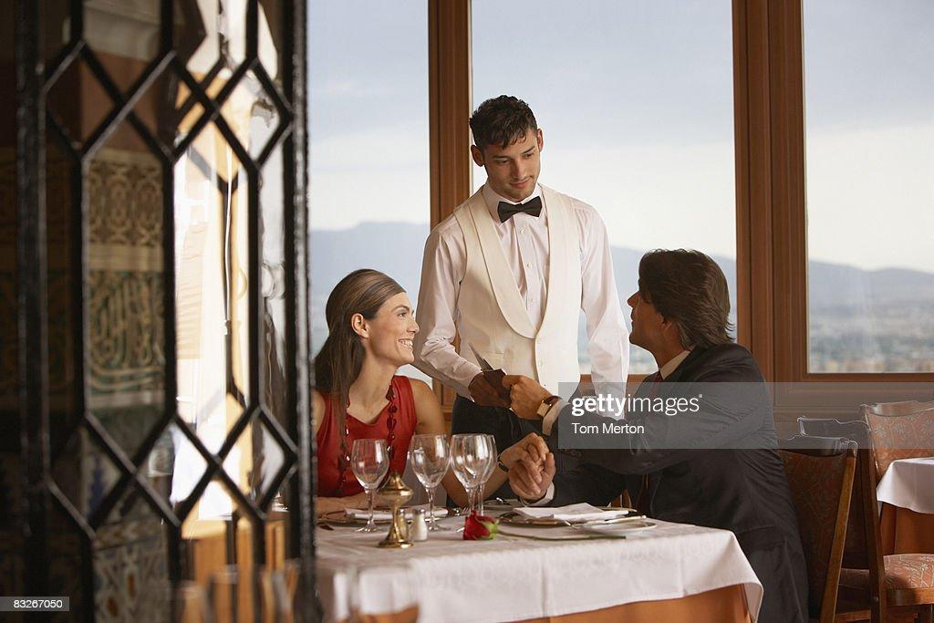 Garçon de café servant un couple dans un restaurant élégant : Photo