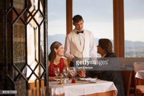 Waiter serving couple in elegant restaurant : Stock Photo