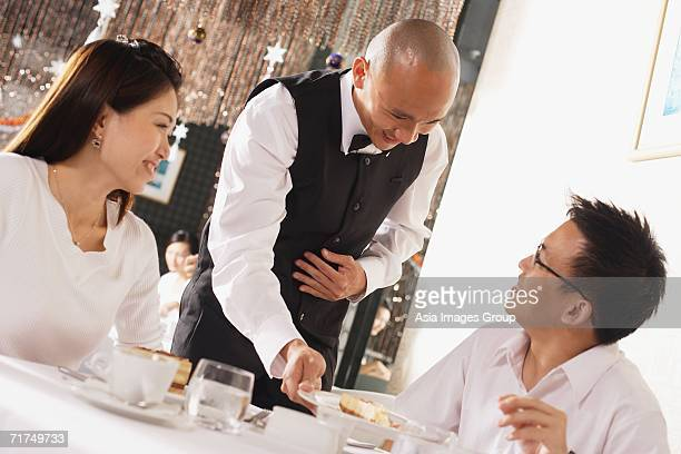 Waiter serving customers in restaurant