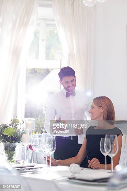 Waiter serving dinner to woman in elegant restaurant