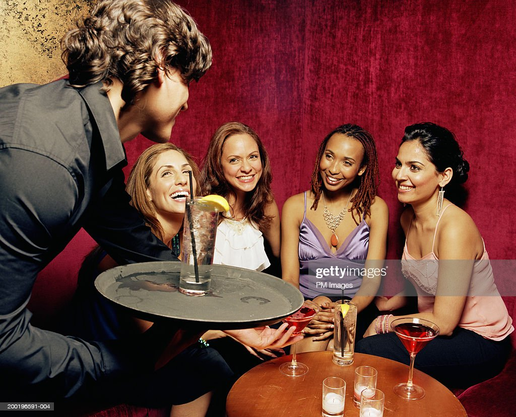 Waiter serving drinks to women, smiling : Stock Photo