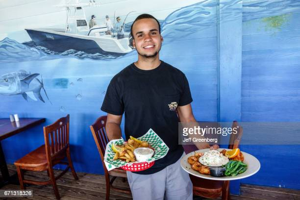 A waiter serving food at Original Tiki Bar Restaurant
