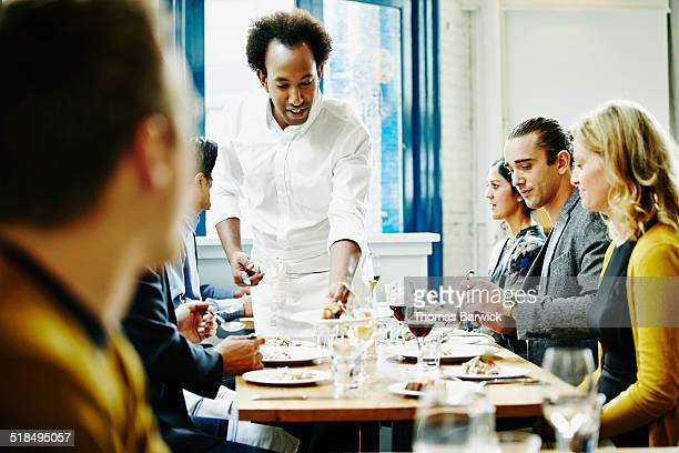 Waiter serving food to couples in restaurant