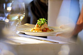 Soft focus Photo, clean, abstract, contemporary shot of waiter serving meal to a table.