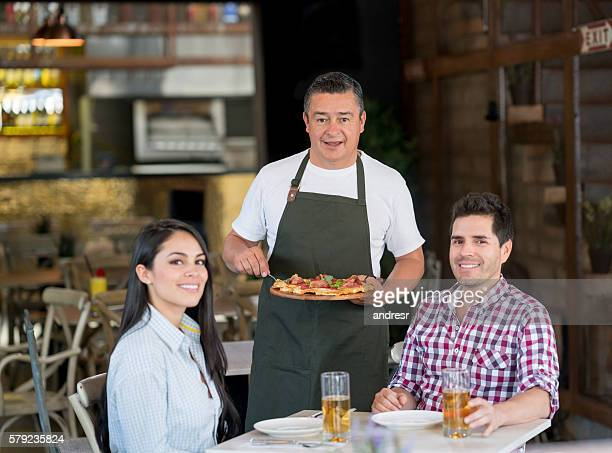 Waiter serving people at a restaurant