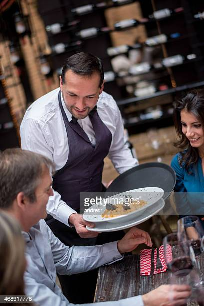 Waiter serving plates at a restaurant
