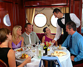 Waiter serving table of five in ship's dining room
