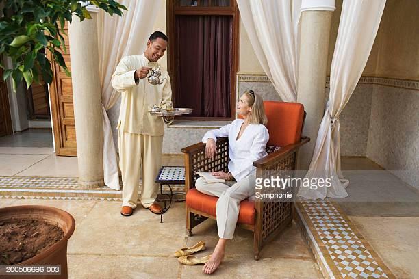 Waiter serving tea to mature woman