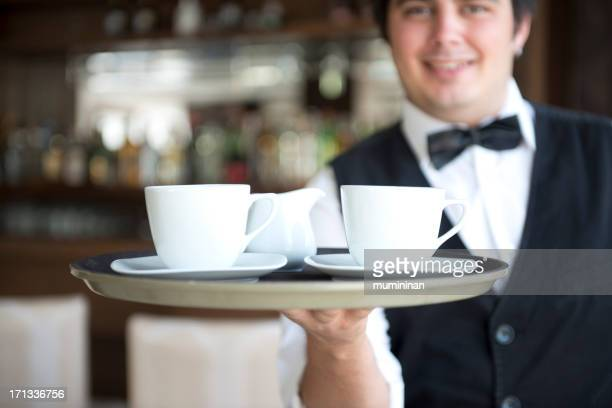 Waiter serving two cups of coffee