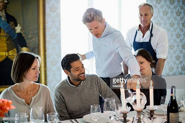 Waiter serving water to business people at restaurant with chef standing in background