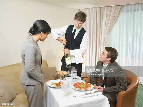 Waiter serving wine to couple in hotel room