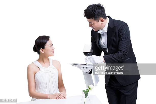 Waiter serving woman wine