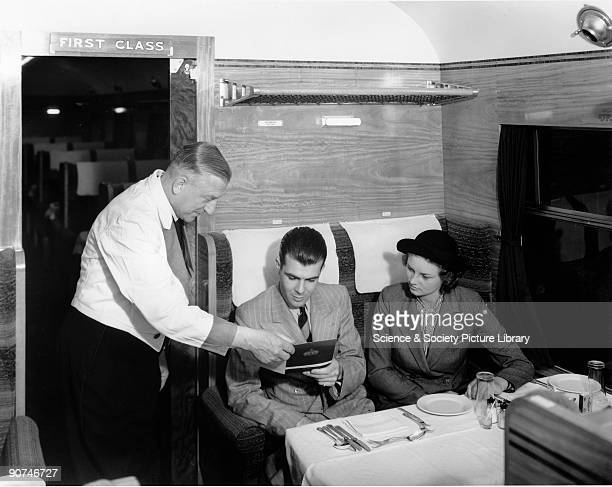 Waiter serving young couple in the dining car of the London Midland Scottish Railway Coronation Scot service from London Euston to Glasgow