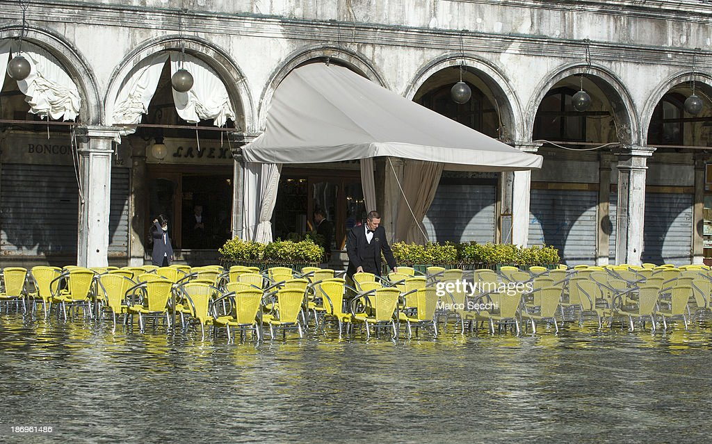 A waiter sets the tables in Saint Mark's Square during today's Acqua Alta on November 5, 2013 in Venice, Italy. The high tide, or acqua alta as it is locally known, is a natural event most commonly affecting the city during Autumn and Winter.