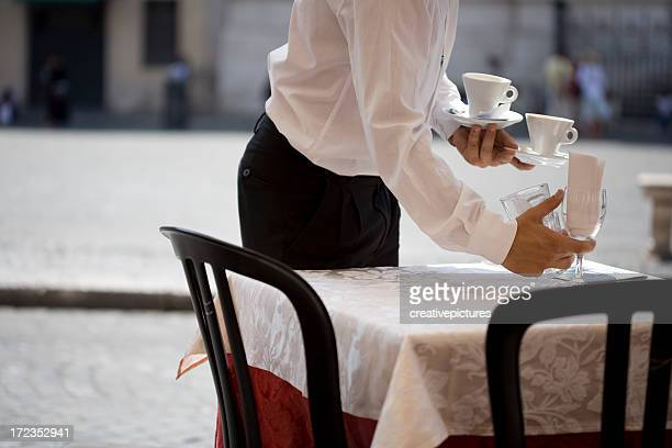 A waiter setting a table in a restaurant