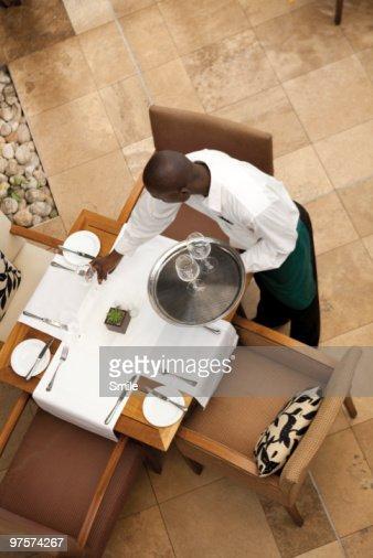 Waiter setting up table : Stock Photo