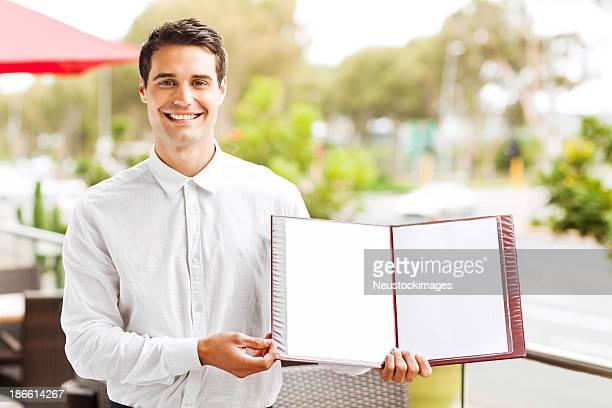 Waiter Showing Blank Menu In Restaurant