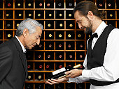 Waiter showing bottle of wine to senior man in restaurant