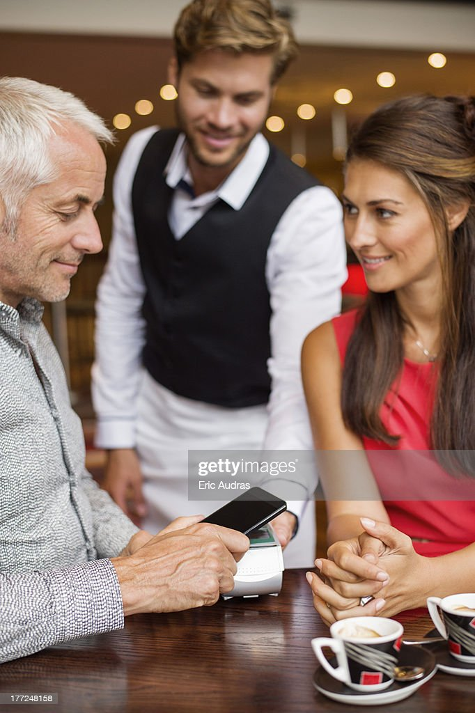 Waiter showing credit card reader to a couple on a table in a restaurant