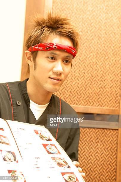 Waiter showing menu at restaurant